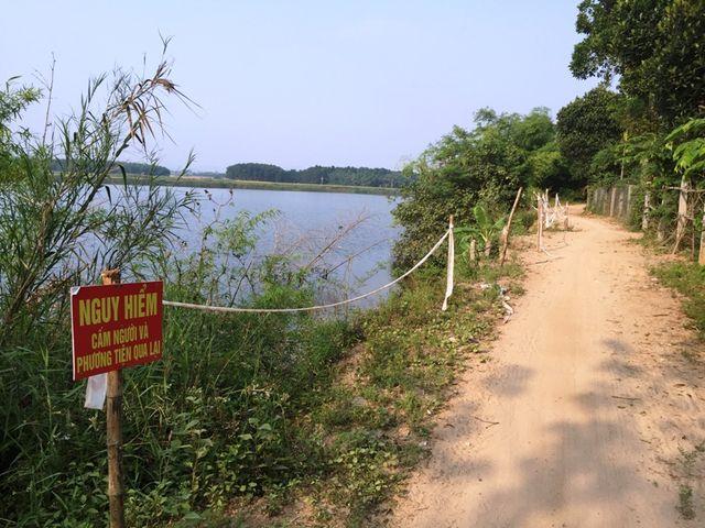 Người dân cắm biển cảnh báo bên bờ sông để hạn chế người dân qua lại.
