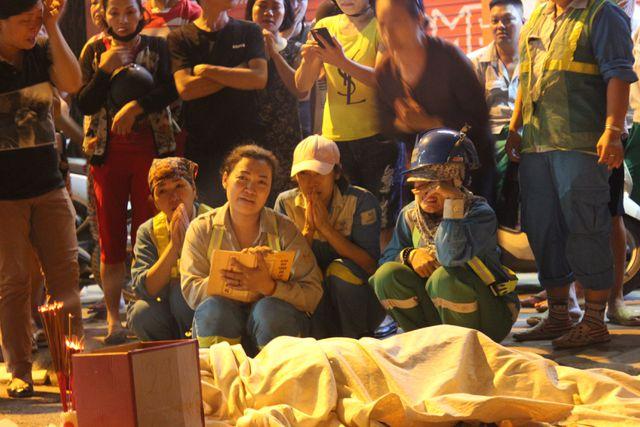 Các đồng nghiệp ngồi khóc, thương xót trước sự ra đi của nữ công nhân vệ sinh môi trường (Ảnh: Nguyễn Trường).