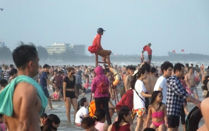Bảo vệ ngồi trên cao để quan sát hướng dẫn du khách tắm biển được an toàn