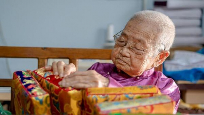 Cụ Huệ gần trăm tuổi vẫn miệt mài gìn giữ nghề làm gối trái dựa cung đình (Ảnh: Éternité Việt Nam).