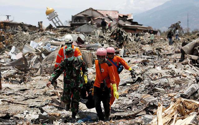 Đội cứu hộ và quân đội đưa các nạn nhân ra khỏi khu vực đổ nát do thảm họa tự nhiên (Ảnh: Reuters).