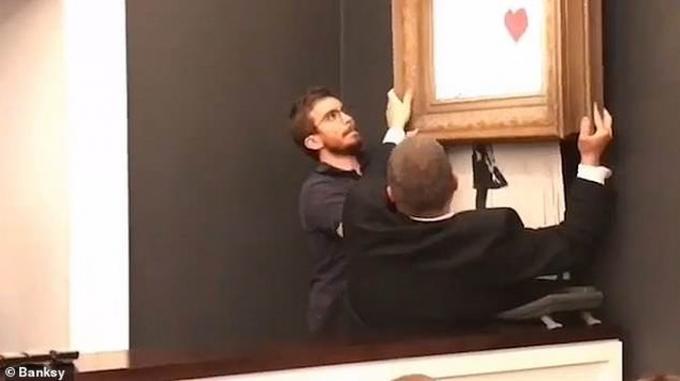 Các nhân viên của nhà bán đấu giá nhanh chóng tháo dỡ bức tranh. Banksy là một họa sỹ bí ẩn, mặc dù vậy, các tác phẩm của ông từ lâu đã được thế giới nghệ thuật đương đại phương Tây biết đến và đánh giá cao. Ảnh: Banksy.