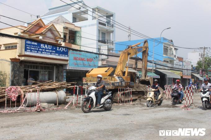 Người tham gia giao thông căng mình luồn lách qua những lô cốt, rào chắn.