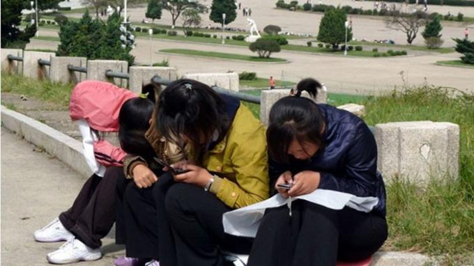 Các cô gái trẻ ở Triều Tiên sử dụng điện thoại di động tại công viên - Ảnh: AFP.