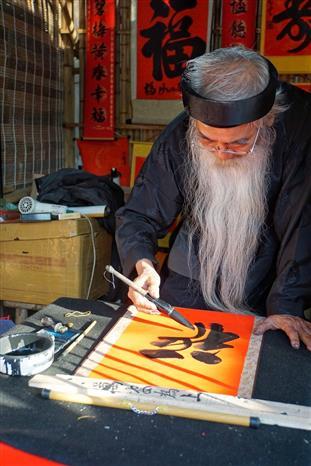 Ông đồ già đang cho chữ tại Văn Miếu-Quốc Tử Giám. Ảnh: Khánh Hòa/TTXVN phát.