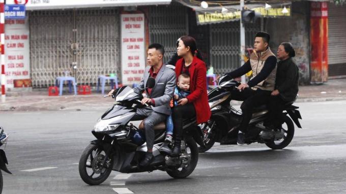 Người dân vô tư đi xe không đội mũ bảo hiểm trong những ngày Tết.