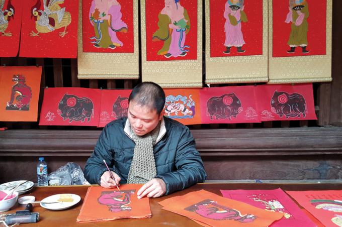Nhiều năm qua, anh Đào Đình Trung, xã Vân Canh, Hoài Đức, Hà Nội, luôn tâm huyết phục hồi dòng tranh Kim Hoàng.Ảnh: Đinh Thuận/TTXVN.