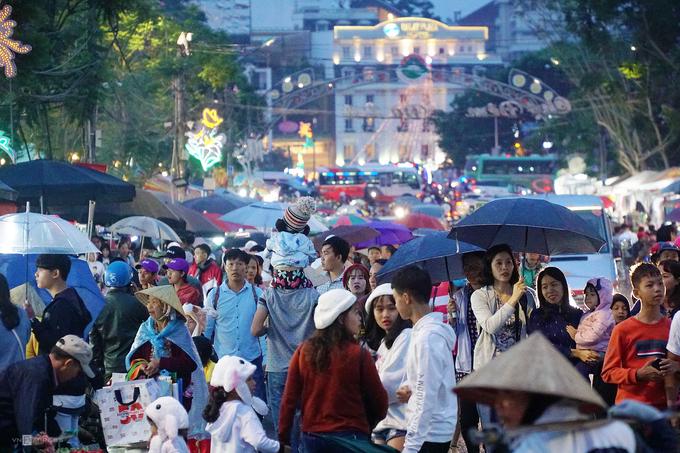 Trước đó, khoảng 18h, trời đổ mưa nhẹ. Đang trong kỳ nghỉ cùng gia đình, anh Minh Ngọc (du khách TP HCM) dùng dù (ô) để che cho con gái trong lúc vào chợ.