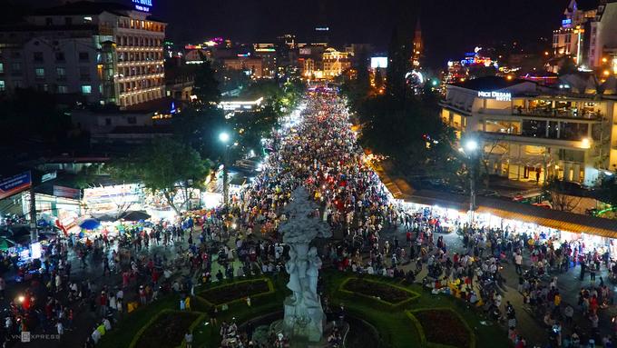 19h ngày 28/4, từng đoàn du khách nườm nượp đổ về chợ Đà Lạt để tham quan, mua sắm và ăn uống. Hai bên chợ là các quán ăn, sạp quần áo.