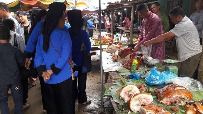Người Tày- Nùng vận quần áo dân tộc đi mua thịt lợn quay về đãi khách. Ảnh: Duy Chiến.