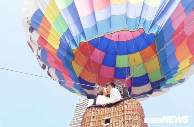 Người dân, du khách thích thú trải nghiệm bay khinh khí cầu trong sáng 1/5.Đôi bạn trẻchụp ảnh cưới, ghi lại khoảng khắc khó quyên trên khinh khí cầu ở độ cao30 đến 50m.