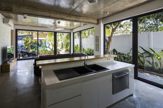 Bếp và phòng khách nằm ở tầng trệt xây dựng theo kiến trúc mở, gần gũi với thiên nhiên và môi trường xung quanh.