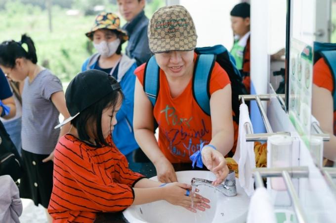 Các bạn nhỏ được bố mẹ hướng dẫn rửa tay cẩn thận trước khi vào tham quan Trang trại.