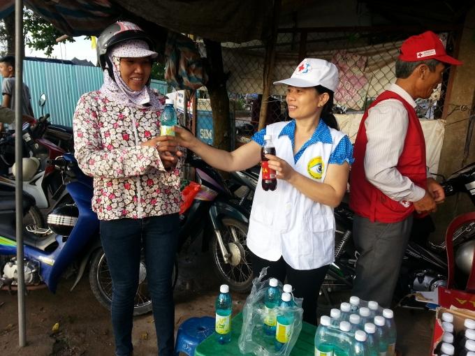 Phụ huynh này vui mừng khi được nhận nước uống miễn phí từ các tình nguyện viên.