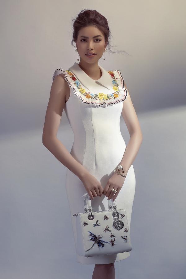 Váy trắng tối giản có điểm nhấn tay áo hình cánh hoa cúc và điểm xuyết chi tiết hoa đính kết 3D dọc theo cổ thuyền được Phạm Hương kết hợp với túi xách cùng màu đính hoạ tiết chuồn chuồn bằng đá cực kỳ sang trọng và thanh lịch.