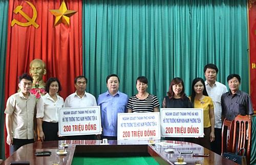 Đại diện lãnh đạo ngành GDĐT Hà Nội trao hỗ trợ cho các trường bị ngập úng của huyện Chương Mỹ