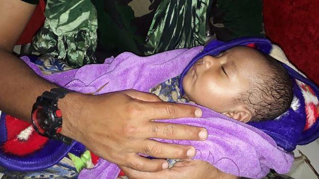 Hình ảnh em bé năm tháng tuổi được may mắn cứu sống. Nguồn: AFP.