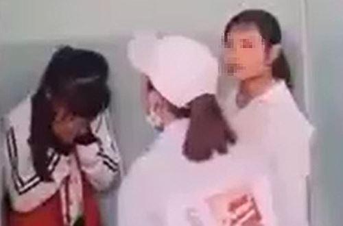 Nữ sinh lớp 7 (trái) bị vây đánh trong nhà vệ sinh ở Phú Yên, hôm 15/3. Ảnh:Cắt từ video.