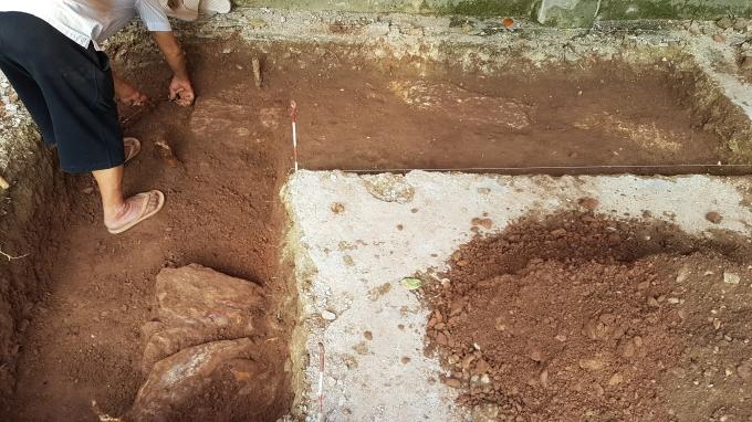 Dấu vết các lớp đá xếp ngay ngắn thành 2 hàng trùng với hình hố khảo cổ chữ L nghi là móng của tường thành xưa.