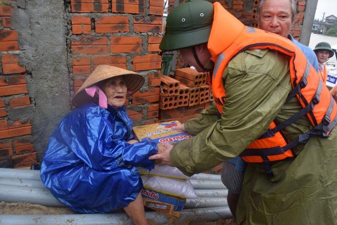 Trung tá Lê Hồng Hà tặng quà cứu trợ bão lụt cho nhân dân vùng ngập lụt.