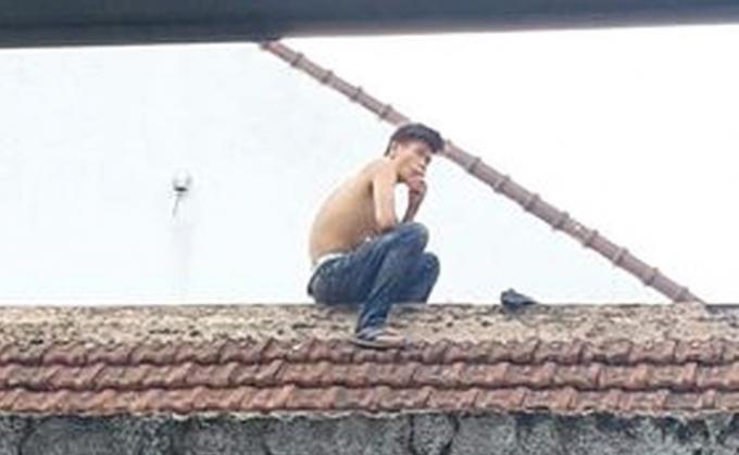Nam thanh niên nghi ngáo đá cố thủ hòa hét trên mái nhà. (Ảnh: MĐ)