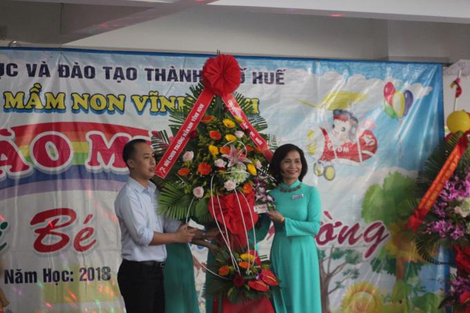Cô Phan Thị Bạch Huệ đón nhận hoa chúc mừng từ đại diện hội phụ huynh .
