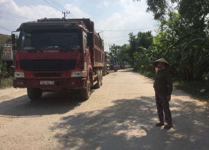 Đoàn xe tải nối đuôi nhau nằm yên bất động vì rào chắn của người dân chưa được tháo dở.