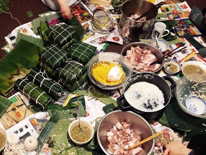 Mọi người quây quần bên nhau gói những chiếc bánh chưng mang hương vị truyền thống để đón tết cổ truyền