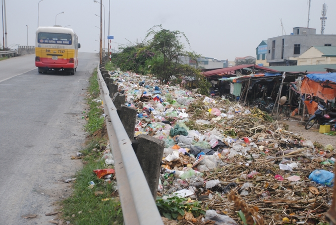 Rác thải ngập tràn chân cầu vượt chợ Lai Cách, thị trấn Lai Cách (Ảnh: Kiên Cường).