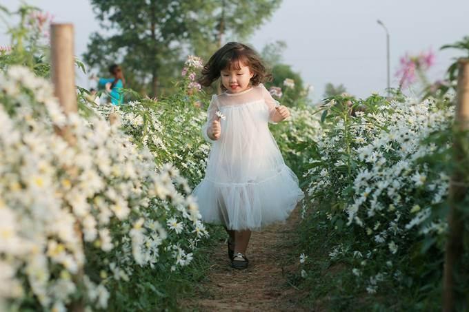 Thiên thần bé nhỏ vui đùa bên những luống hoa.