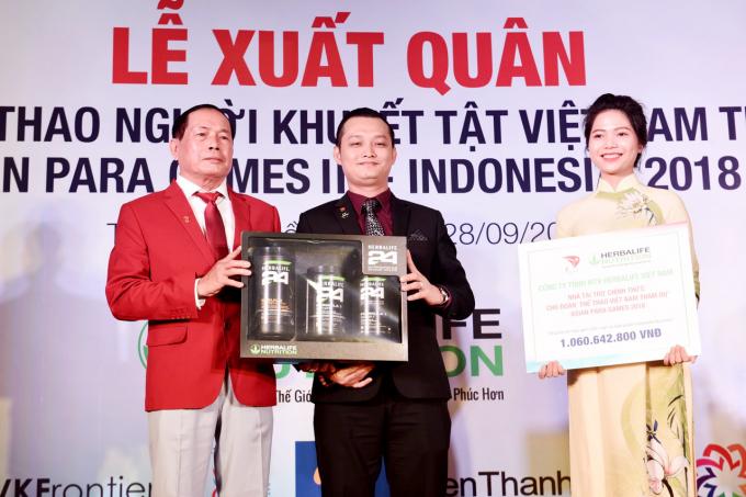 Ông Phạm Tường Huy, Tổng giám đốc Herbalife Việt Nam trao bảng tài trợ và sản phẩm dinh dưỡng tượng trưng cho Trưởng đoàn thể thao NKT Việt Nam tại lễ xuất quân