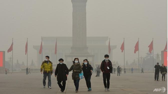 Du khách đeo mặt nạ tại Quảng trường Thiên An Môn khi ô nhiễm không khí nặng nề che phủ Bắc Kinh.(Ảnh: AFP)