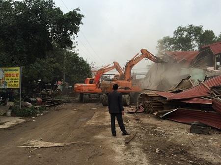 Một vị lãnh đạo quận Nam Từ Liêm đứng chỉ đạo hai chiếc máy xúc tiến hành cưỡng chế nhà ông Minh biến thành đống đổ nát ngày 28/12/2015. (ảnh Đông Bắc)