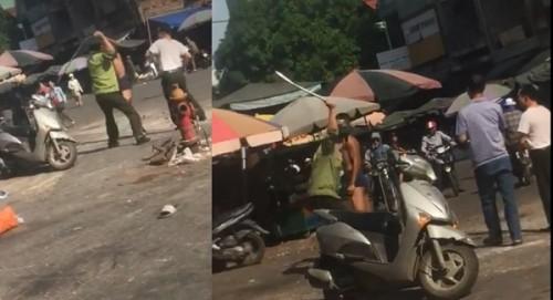Hình ảnh người đàn ông mặc đồng phục áo bảo vệ dùng vật cứng đánh vào người nam thanh niên.