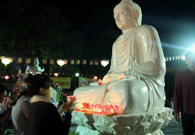 Mỗi người cầm một ngọn đèn được châm sáng từ ngọn đèn dưới chân Đức Phật.