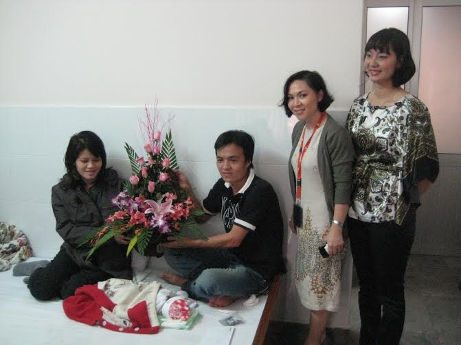 Đại diện Jetstar Pacific thăm và tặng hoa cho chị Nguyễn Thị Lập sinh bé trai trên máy bay năm 2011.