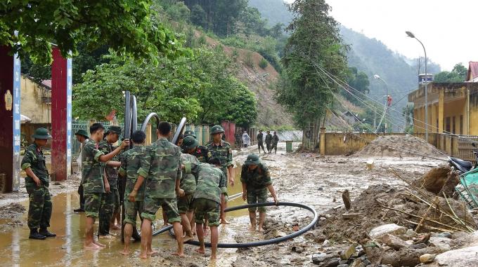 Lực lượng chức năng và người dân dọn dẹp nhà cửa, vệ sinh đường phố sau lũ.