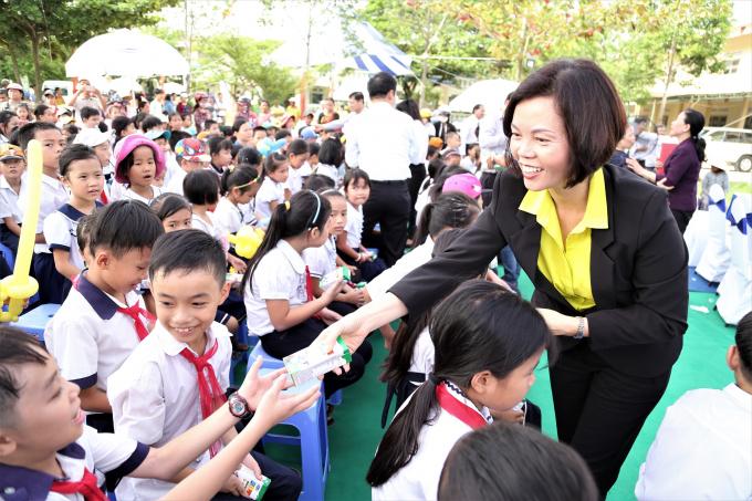Bà Bùi Thị Hương – Giám đốc Điều hành Vinamilk trao sữa cho các em học sinh.