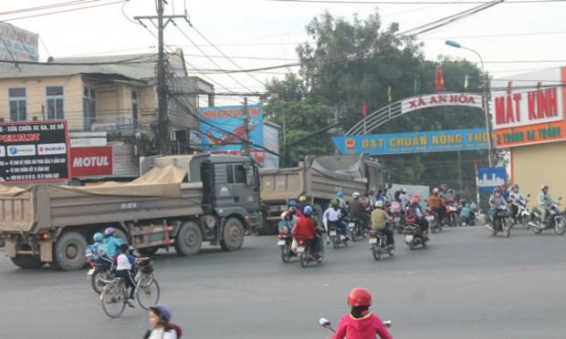 Xe ben chạy thành từng tốp trên đường nông thôn mới đang xuống cấp.