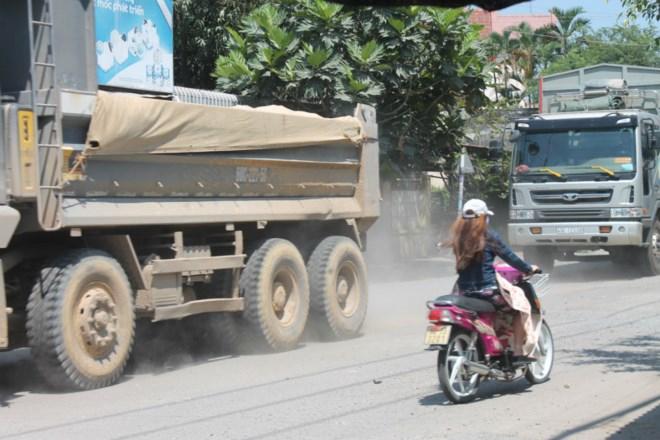 Xe ben cuốn theo bụi vào nhà dân bên đường.