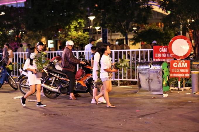 Ở ngoài đường, nhiều người vẫn kiên trì đợi các xe hoa đi ra để lấy những chậu hoa mà mình thấy là còn có thể sử dụng được. Ảnh: Trường Sơn