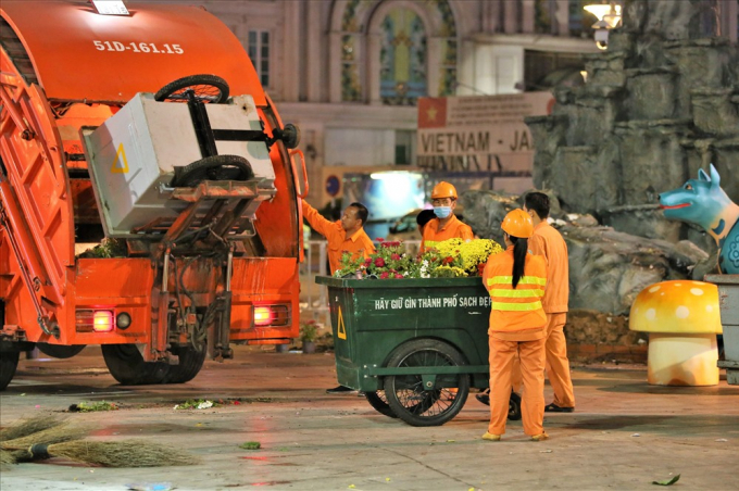 Đúng 22h, hàng chục xe ép rác cùng hàng trăm công nhân được huy động để thu dọn đường hoa Nguyễn Huệ. Ảnh: Trường Sơn