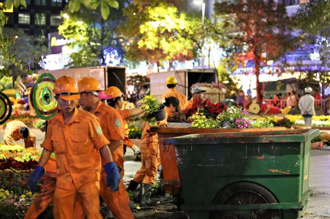 Hàng nghìn chậu hoa các loại sau nhiều ngày trang trí trên đường hoa được công nhân cho vào các xe đẩy để đưa ra xe ép rác chuyên dụng. Ảnh: Trường Sơn