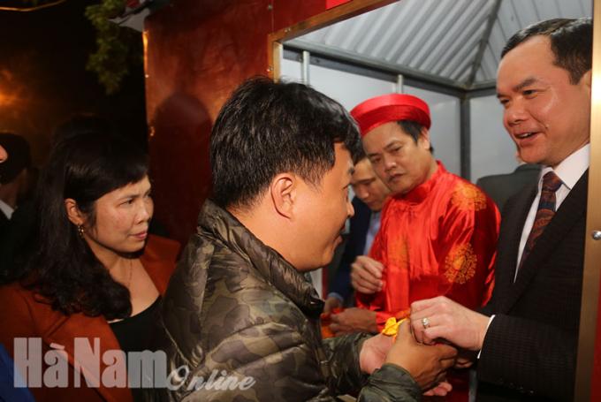 Bí thư Tỉnh ủy Hà NamNguyễn Đình Khang phát lương cho du khách về dự lễ hội đền Trần Thương năm 2018.