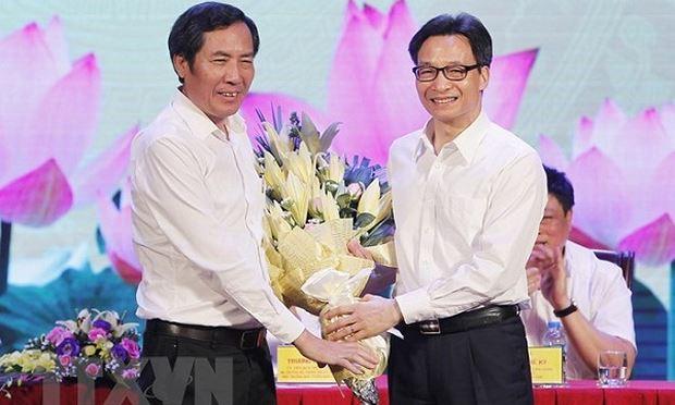 Phó Thủ tướng Vũ Đức Đam (bên phải) tặng hoa Chủ tịch Hội Nhà báo Việt Nam Thuận Hữu, chúc mừng những người làm báo trên cả nước