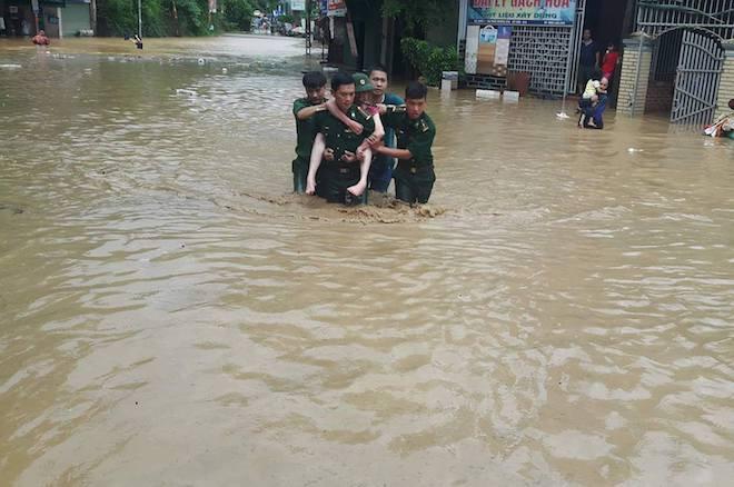 Các chiến sỹ biên phòng cõng người dân ra khỏi nơi ngập lụt. (Ảnh: Hải Thượng).