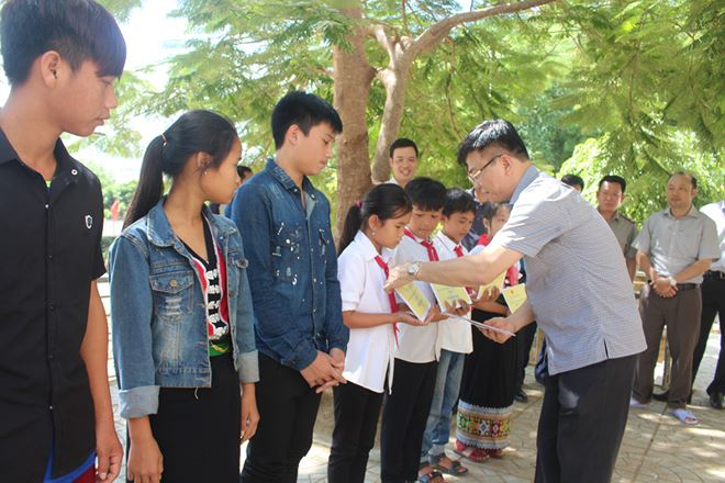 Động viên học sinh vượt khó khăn, nỗ lực học tập, Bộ trưởng đồng thời tặng quà cho các em.