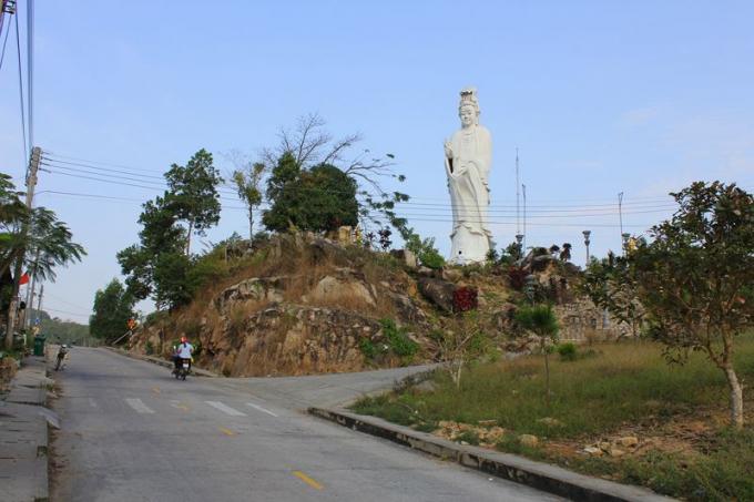 Đường lên đỉnh núi Cấm có tượng Phật bà Quan âm đứng sừng sững ở một ngọn đồi bên phải như chào đón.