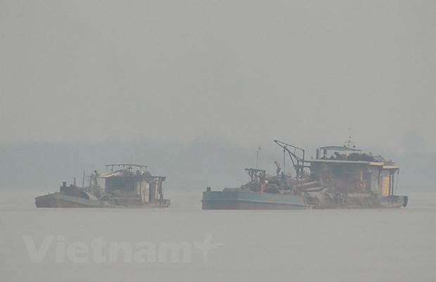 Các tàu hút sau khi dùng vòi rồng hút cát, sẽ được sàng lọc để lấy cát đen, còn rác đổ lại xuống sông. (Ảnh: PV/Vietnam+)