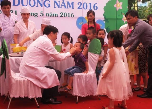 Thứ trưởng Bộ Y tế Nguyễn Thanh Long cho trẻ nhỏ uống thuốc bổ sung vi chất.